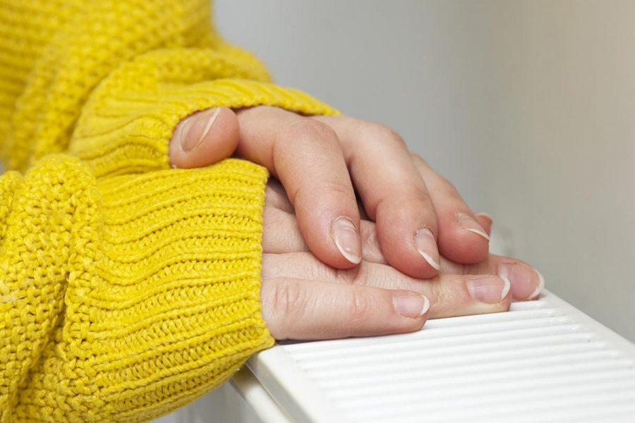 woman-warms-her-hands-radiator